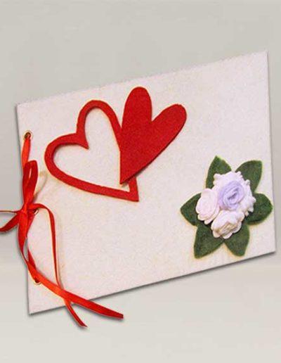 Album foto artigianale rivestito con feltro bianco, con rose bianche e cuori rossi.
