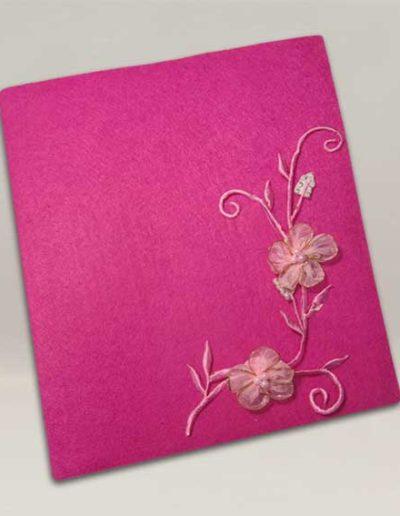Album foto artigianale rivestito con feltro fucsia e un ramo di fiori di raso rosa