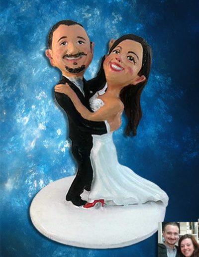 Cake topper sposi di terracotta raffiguranti due sposi abbracciati mentre ballano. Lei ha le scarpe rosse. Fatto a mano