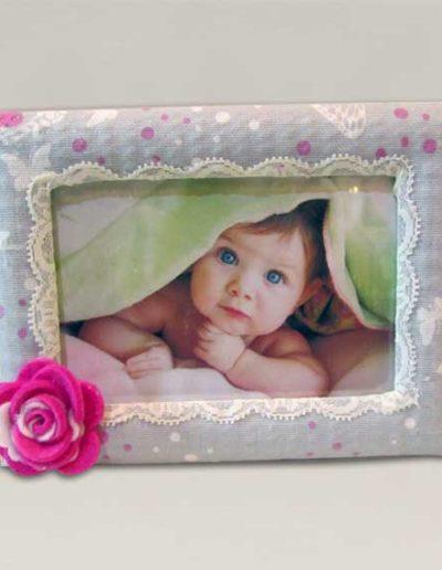portafoto artigianale rivestito in tessuto e con una rosa di feltro a decorazione.