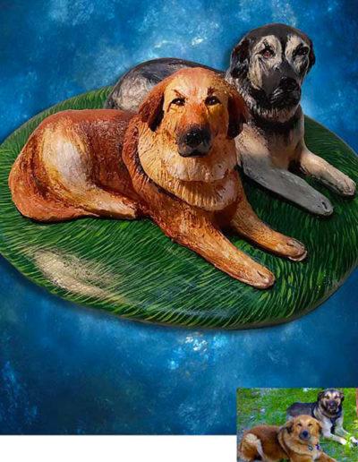 Statuine in terracotta di due cagnolini meticci . Uno color crema l'altro scuro appoggiati su una base di terracotta dipinta come un prato. Fatto a mano