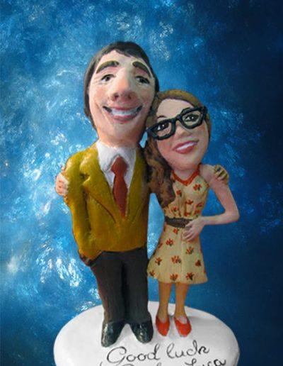 Statuina di terracotta di una coppia di fidanzati abbracciati con viso caricaturato e scritta sulla base. Fatto a mano.