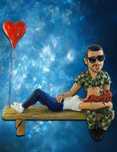 Statuina di terracotta di una coppia di fidanzati seduti su una panchina , lui vestito da militare , lei sdraiata e con un palloncino a forma di cuore. Fatto a mano