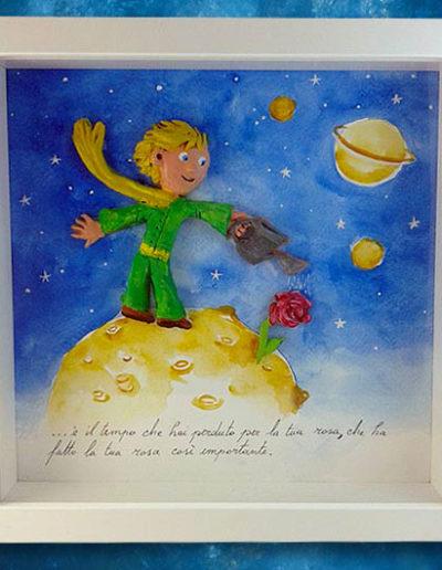 Cornice quadrata con bassorilievo a colori del Piccolo Principe che innaffia la sua rosa e frase del libro sul fondo dipinto a mano con acquerello. Fatto a mano