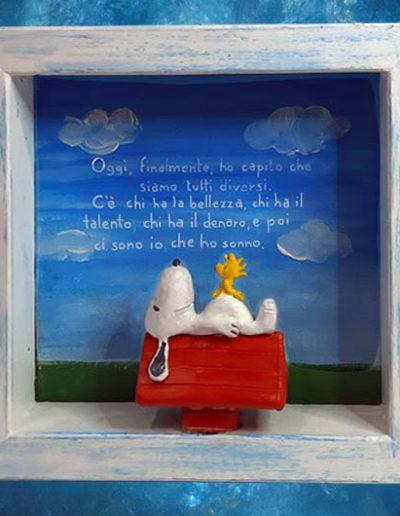 Statuina di terracotta del fumetto Snoopy e Woodstock inserita in una cornice di legno massello bianca e azzurra con scritta sul fondo dipinta con colori acrilici. Fatto a mano