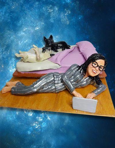 Statuina di terracotta, in pigiama a righe di seta, sdraiata vicino al letto mentre lavora sul notebook con i suoi cagnolini che dormono beatamente sul letto. Fatto a mano