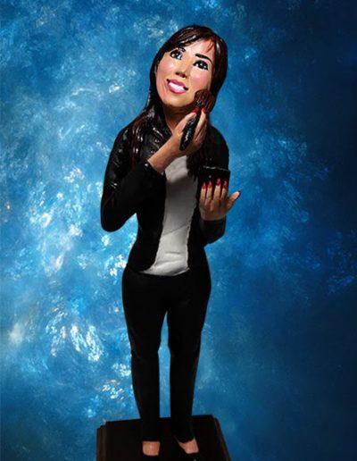 Statuina di terracotta di una ragazza in piedi , vestita di nero, mentre si trucca. Fatto a mano