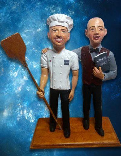 Coppia di statuine di terracotta: un pizzaiolo con cappello da cuoco e pala da forno in mano e un direttore di sala con menù in mano. Fatto a mano.