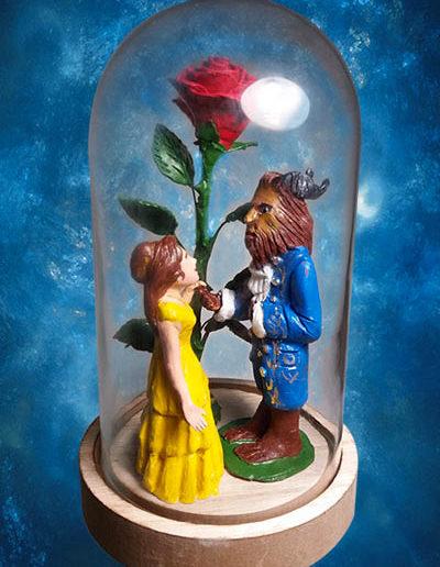 Statuine di terracotta di terracotta della Bella e la Bestia dentro la campana di vetro con la rosa incantata del film di animazione. Fatto a mano