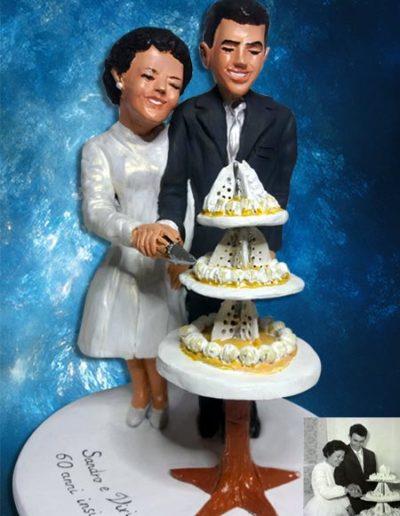 Cake topper sposi di terracotta per 60 anniversario, raffiguranti due sposi al taglio della torta. Fatto a mano