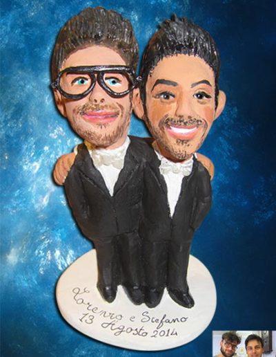 Cake topper sposi di terracotta raffiguranti due ragazzi abbracciati. I visi sono caricaturati. Fatto a mano