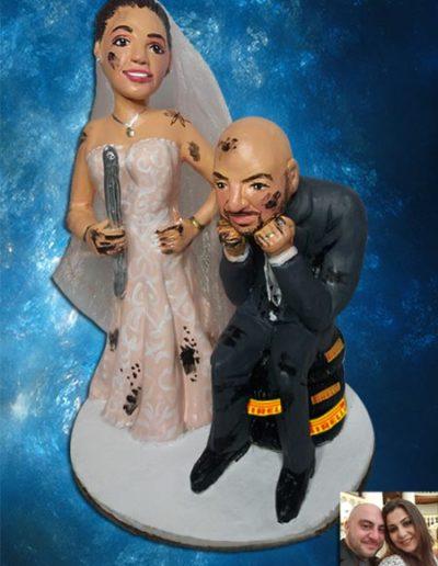 Cake topper di terracotta, raffigurante due sposi uno seduto su treno di pneumatici e la sposa con la chiave per togliere le camere d'aria. Entrambi macchiati di olio motore. Fatto a mano