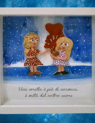 Cornice quadrata con bassorilievo a colori di due bambine con palloncini a cuore, con frase su sorelle sul fondo dipinto a mano con acquerello. Fatto a mano