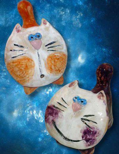Statuine di ceramica di due gatti stilizzati uno arancione e uno viola. Fatto a mano.