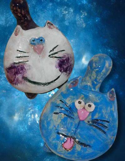 Statuine in ceramica lucida di due gatti stilizzati con faccia piatta. Fatto a mano