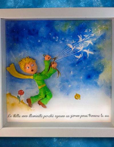 Cornice quadrata con bassorilievo a colori del Piccolo Principe che torna sul suo pianeta volando via e frase del libro sul fondo dipinto a mano con acquerello. Fatto a mano