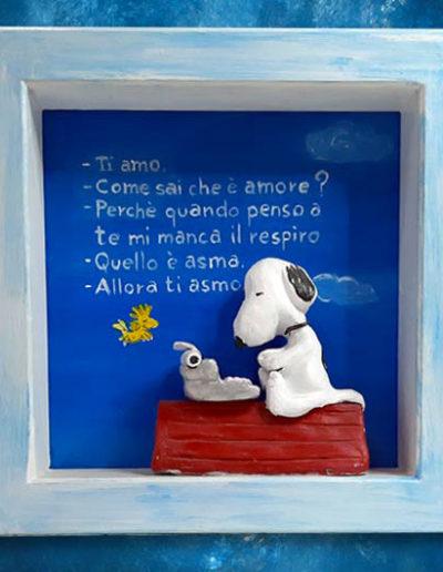 Statuina di terracotta del fumetto Snoopy all'interno di una cornice di legno massello bianca con scritta sul fondo dipinta con colori acrilici. Fatto a mano