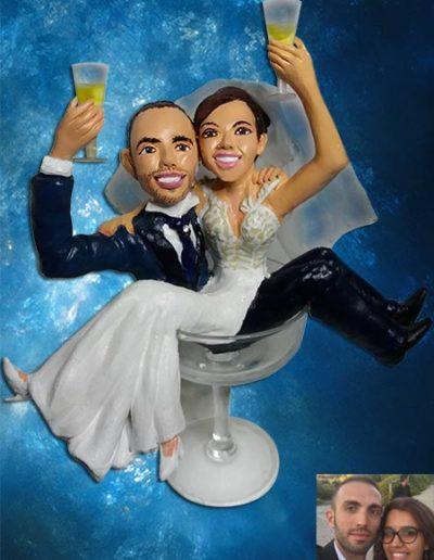 Cake topper di terracotta, raffigurante due sposi seduti dentro un bicchiere di vetro. Fatto a mano