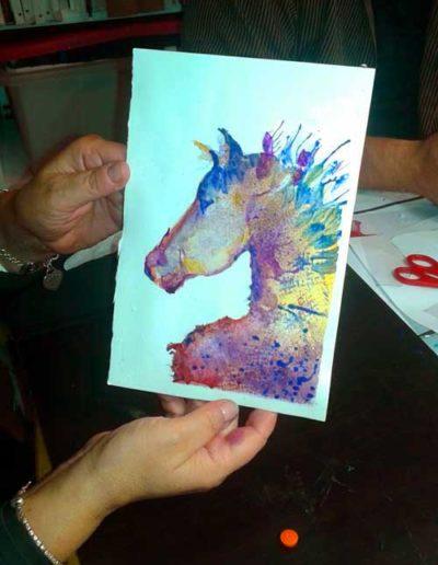 Dipinto ad acquerello dipinto da allievi raffigurante la sagoma di un cavallo multicolor.